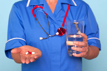 Photo of a nurse in uniform holding some pills and a glass of water photo