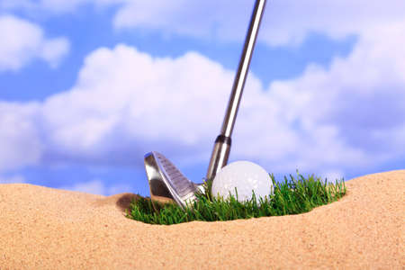 traps: Golf concept photo of a ball lying on a patch of grass in a bunker. Stock Photo