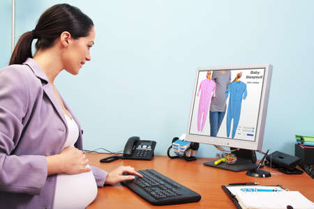 Photo of a pregnant businesswoman in her office shopping online for baby clothes. The screenshot is a mock up and is one of my shots. Screen has a clipping path to add your own image or text. Stock Photo - 9969728
