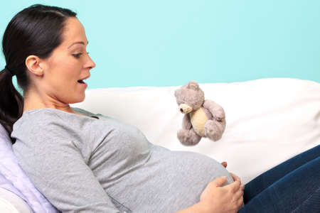 experiencing: Photo of a pregnant woman lying on a sofa experiencing her babys first kick, look of surprise on her face as the small teddy bear jumps in the air. Slight motion blur on the bear.
