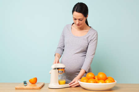Photo of a 32 week pregnant woman in her kitchen preparing freshly squeezed orange juice. photo