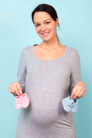 unknown gender: Photo of a woman who is 32 weeks pregnant holding baby booties, pink for a girl and blue for a boy. Stock Photo