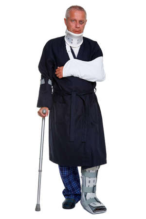Photo of a mature male with various injuries on a crutch, hes wearing a neck brace, arm sling and leg cast and has a black eye, isolated on a white background.  photo