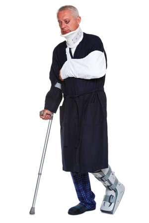 neck brace: Photo of a mature male with various injuries using a crutch, hes wearing a neck brace, arm sling and leg cast and has a black eye, isolated on a white background.  Stock Photo