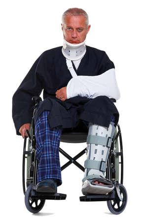 jambe cass�e: Photo d'un homme mature avec diverses blessures dans un fauteuil roulant, il porte un pl�tre minerve, �charpe et la jambe et a un oeil au beurre noir, isol� sur un fond blanc.