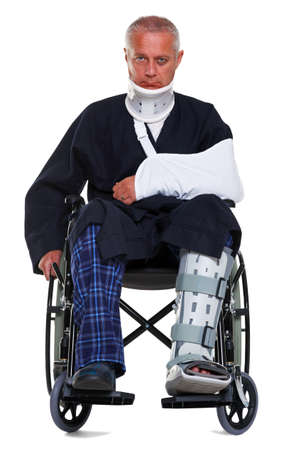 Photo of a mature male with vaus injuries in a wheelchair, he's wearing a neck brace, arm sling and leg cast and has a black eye, isolated on a white background.  Stock Photo - 9969745