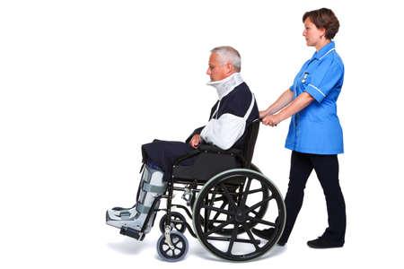 pushing: Foto van een gewonde man in een rolstoel met een vrouwelijke verpleegster duwen hem, geïsoleerd op een witte achtergrond. Stockfoto