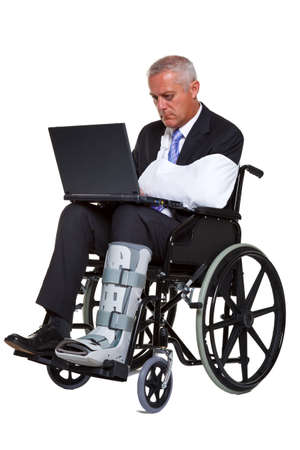 work injury: an injured businessman sitting in a wheelchair working on a laptop computer, isolated against a white background.