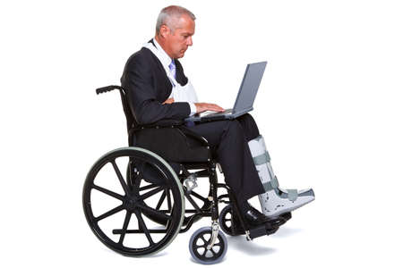 broken leg: an injured businessman sitting in a wheelchair working on a laptop computer, isolated against a white background.