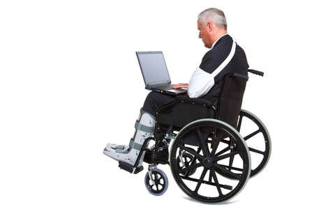 Photo of an injured businessman sitting in a wheelchair working on a laptop computer, isolated against a white background.  photo