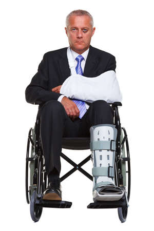 leg injury: an injured businessman sitting in a wheelchair, isolated against a white background.