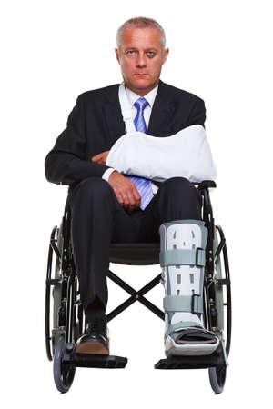 accidente laboral: un hombre de negocios lesionado sentado en una silla de ruedas, aislado sobre un fondo blanco.