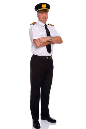 an airline pilot wearing the four bar Captains epaulettes arms folded, isolated on a white background. photo