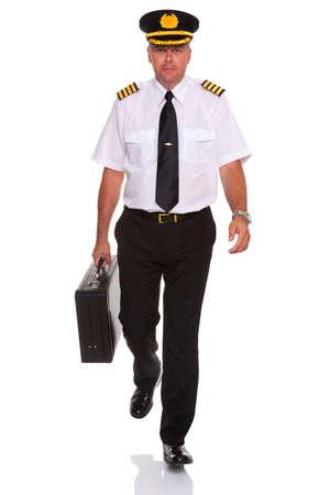 piloto: Foto de un piloto de aerolínea luciendo los cuatro capitanes charreteras caminando hacia la cámara de transporte su vuelo, aislado en un fondo blanco de la barra.