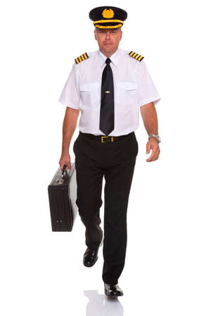 Photo of an airline pilot wearing the four bar Captains epaulettes walking towards camera carrying his flight case, isolated on a white background. photo