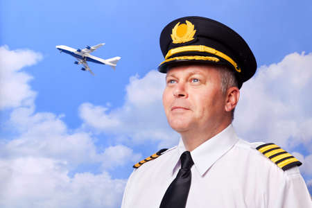 pilotos aviadores: Foto de un piloto de aerolínea con cuatro barras charreteras de capitanes, disparó contra un fondo de cielo con jet jumbo despegando en la distancia. Foto de archivo