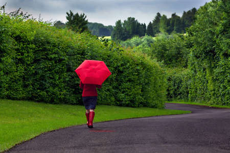 walking down: Photo of a woman walking down a road holding a red umbrella after a heavy downpour of rain on an overcast day. Stock Photo