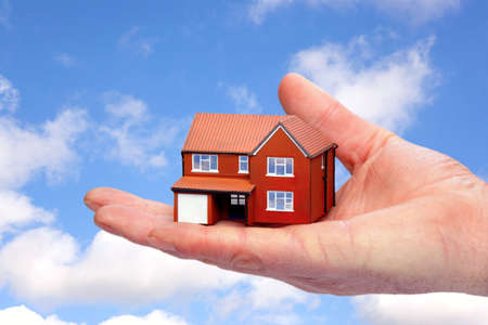 Photo of a hand holding a model house against a sky background. photo