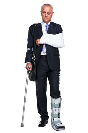 negligence: Badly injured businessman walking on cructhes carrying a briefcase, isolated on a white background.