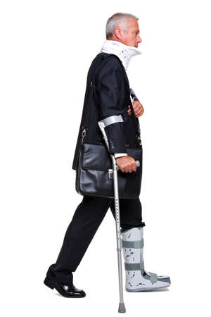 badly: Badly injured businessman walking on cructhes carrying a briefcase, isolated on a white background.