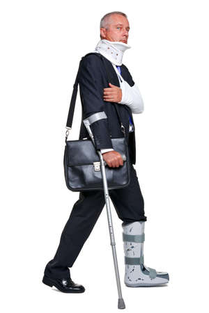 Badly injured businessman walking on cructhes carrying a briefcase, isolated on a white background. photo