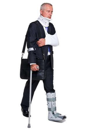pierna rota: Herido de empresario caminando sobre cructhes llevando un maletín, aislado en un fondo blanco. Foto de archivo