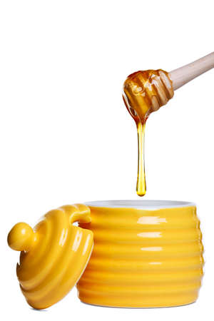 Yellow beehive shaped honey pot with dripping dipper held above, isolated on a white background.  Stock Photo