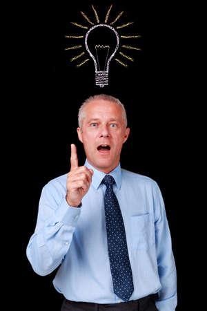 id�e lumineuse: Photo d'un homme d'affaires matures sur un fond noir avec une ampoule de craie tirer dessus de sa t�te pour repr�senter le moment o� il a eu une id�e lumineuse.