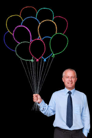 colourful tie: Photo of a mature businessman against a black background holding a bunch of chalk drawn balloons, add your own letters to make a message. Check my portfolio for chalk letters and numbers to use. Stock Photo