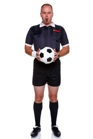 whistles: Full length photo of a football or soccer referee holding a ball with a whistle in his mouth, isolated on a white background. Stock Photo