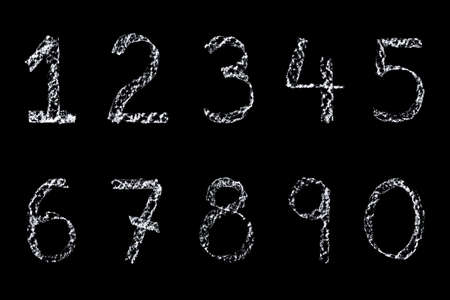 Handwritten numbers written on a blackboard in white chalk then cleaned up during editing and placed on a black background. photo