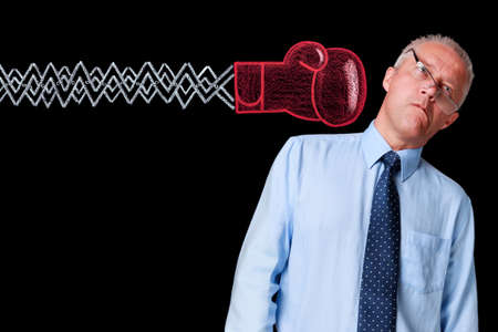 then: Photo of a mature businessman against a black background being delivered a knockout punch by a handrawn chalk boxing glove on expanding mechanical arm.  Boxing glove was drawn on a blackboard then digitally cleaned and added to the image. Stock Photo