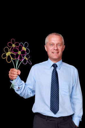 Photo of a mature businessman against a black background holding a bunch of handrawn chalk flowers, flowers were drawn on a blackboard then digitally cleaned and added to the image. photo