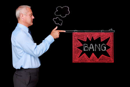 sacked: Photo of a mature businessman against a black background firing a chalk drawn gun with a BANG flag. Gun was drawn on a blackboard then digitally cleaned and added to the image.