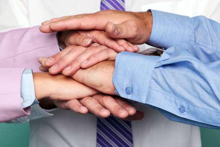 la union hace la fuerza: Foto de tres hombres de negocios de apilamiento manos para representar el trabajo en equipo.