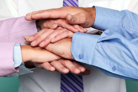 unrecognisable person: Photo of three business people stacking hands to represent teamwork.