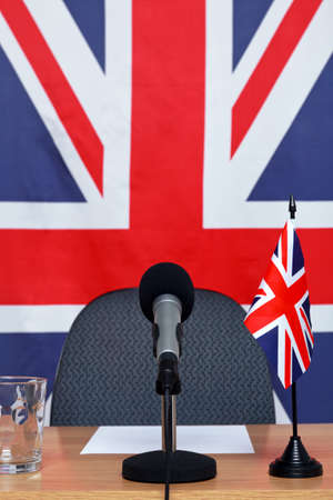 press conference: United Kingdom themed conference desk with microphone and flags.