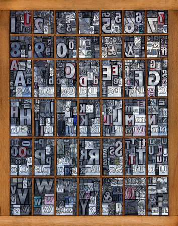 block letters: Photo of a printing tray full of old used metal letterpress in mixed fonts, all the letters of the alphabet and numbers from 0-9 mixed in with some punctuation marks and symbols. Stock Photo