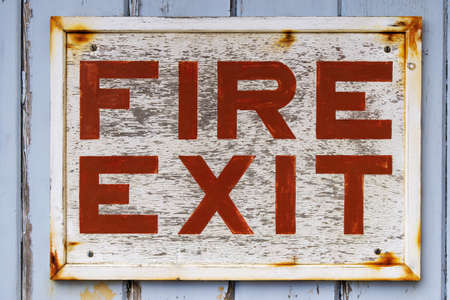 fire exit sign: Photo of an old weathered FIRE EXIT sign on a blue door with peeling paint. Stock Photo