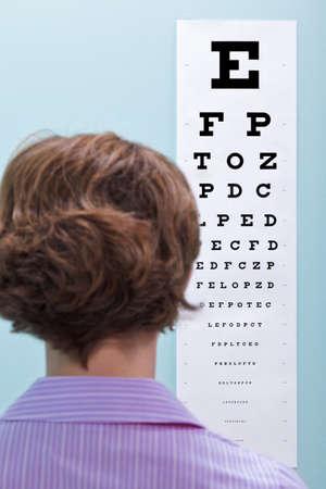 optometria: ZdjÄ™cie kobieta na optykami o jej wzroku badany przy wykorzystaniu wykres oczu czy konieczne ona okularów. Zdjęcie Seryjne