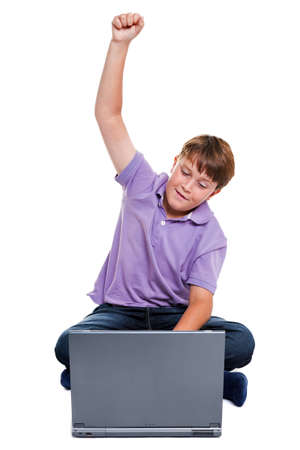 11 year old: Photo of an 11 year old school boy with his arm raised as he looks at his laptop screen, isolated on a white background.
