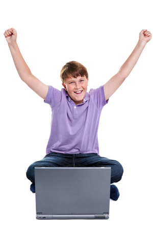 11 year old: Photo of an 11 year old school boy sat with a laptop computer, his arms raised in the air, isolated on a white background. Stock Photo