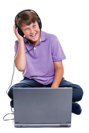 11 year old: Photo of an 11 year old school boy wearing headphones sitting with a laptop computer, isolated on a white background.