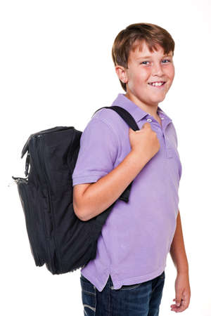 11 year old: Photo of an 11 year old school boy carrying his school rucksack bag, isolated on a white background.