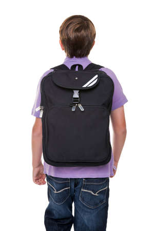 Photo of an 11 year old school boy carrying his school rucksack bag, isolated on a white background. photo