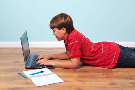 Photo of a boy lying on the floor typing on his laptop computer photo