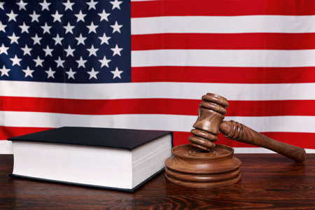 Still life photo of a gavel, block and law book on a judges bench with the American flag behind. photo