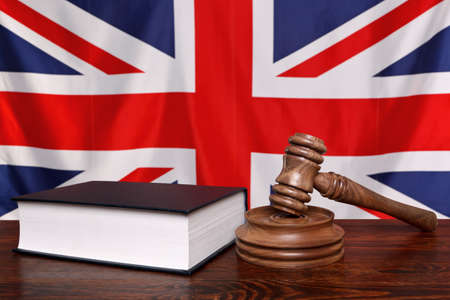 court room: Still life photo of a gavel, block and law book on a judges bench with the United Kingdom union jack flag behind.