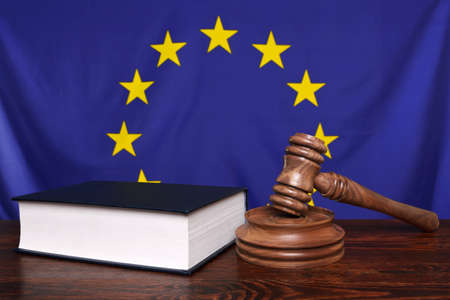 Still life photo of a gavel, block and law book on a judges bench with the European Union flag behind. photo