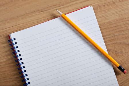 crayon: Photo d'un bloc-notes vierge et un crayon a statu� sur un bureau, ajouter votre propre copie.